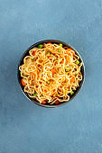 Instant noodles with carrot, scallions, and a sauce, a vegetable soba bowl, top-down shot with copyspace