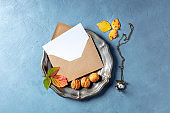Autumn stationery mockup, overhead flat lay shot of a greeting card or invitation in a brown craft envelope, on a tray with leaves and nuts