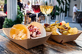 Tapas bar. Cheese, ham and pinchos with glasses of red and white wine on a wooden table in an outdoors cafe