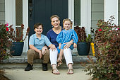 a single mother sitting outside talking to her two children on the front porch of a new construction home