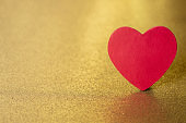 A single red heart on a gold glitter background that sparkles and has lots of copy space
