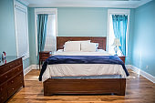 Large blue master bedroom with a king sized bed, furniture and drapes curtains on the windows with hardwood floors