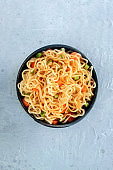 Instant noodles with carrot, scallions, and a sauce, a vegetable soba bowl, overhead shot with copyspace