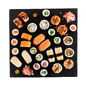 Large sushi set, isolated on a white background with a clipping path, shot from the top. A flat lay of various maki, nigiri and rolls