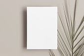 Invitation white card mockup with a palm leaf on a beige table. 5x7 ratio, similar to A6, A5.