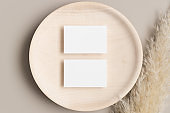 Two white business cards mockup 85x55mm on a wooden plate with a pampas grass decoration.