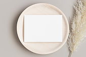 Invitation white card mockup on a wooden plate with a pampas grass. 5x7 ratio, similar to A6, A5.