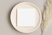 Invitation square card mockup on a wooden plate with a pampas grass.