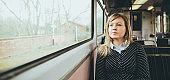 Young woman on a train looking out the window while sitting during travel on a train. Enjoying travel on train or tube. Young woman on train sitting and relaxing. railroad transport. planning route of transport. young woman in train. young woman relaxing