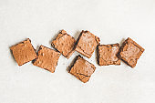 Top view of freshly baked home made brownie cake cut in squares over white rustic background.