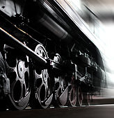 Wheels of an old steam locomotive, trains in motion. Close-up.