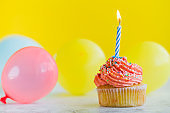 Happy Birthday day cupcake and cake bakery with candles, bright lights bokeh. Background holiday with confetti, balloon and place for text
