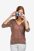 Beautiful and happy woman holding an old photography camera, isolated over a white background
