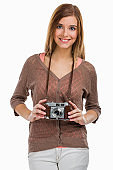 Beautiful and happy woman holding an old photography camera, isolated over a gray background