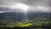 Bright sunlight shining through hole of clouds to dark scene of mountain range, Azores, Sao Miguel, Portugal. The beam of light through the dark clouds on the mountains in Azores, Portugal.
