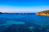 Yacht on lagoon at sunny day. Sailing boat. Yacht in the sea, aerial photography drone. Amazing yacht or sailing boat with a turquoise and transparent sea. Top view of the sailing boats in blue lagoon