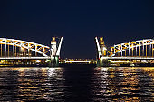 Open bridge in Saint Petersburg, Russia. Bolsheokhtinsky bridge at night. Illumination of the Peter the Great Bridge
