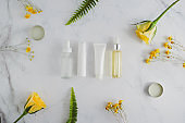 cosmetic skincare set .beauty product packaging mock up on luxury white marble with natural flower.