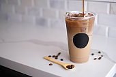 pouring cold coffee with the bean on the marble . ice refreshment in the plastic take away cup.