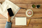 woman use the mobile phone application on wood background in the coffee cafe . flat lay style.