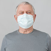 Senior in medical mask isolated on gray background