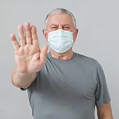 Mature man in medical mask isolated on gray background