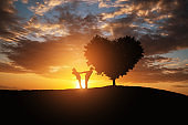 Silhouette of a couple in abstract field with heart shape tree with sunset.Romance and Valentine concept background.