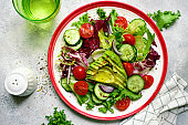 Fresh vegetable salad with avocado, tomatoes, cucumber and red onion