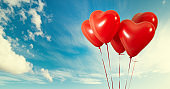 Group of heart shaped red air baloon on blue sky with clouds. Valentines day and romance concept.
