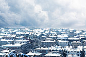 View of the city covered with snow from above and a gray cloudy sky background in the winter season.