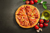 Top view of hot pepperoni pizza,Tasty pepperoni pizza and cooking ingredients tomatoes basil on black background.