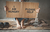 Homeless man showing I am hungry, Please help text on cardboard.