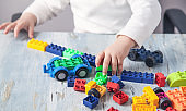 Little girl playing with colorful construction plastic blocks.