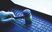Male hand holding Judge gavel on laptop keyboard. Internet crime