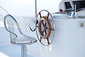 Steering wheel and metal seat on a yacht