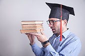 Graduate student holding book in office.