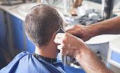 Professional hairdresser using hair cutting machine.