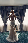 Model bride posing in a hotel by the window.