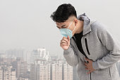 man coughs and wears mask