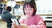 Asian girl play mobile game happily