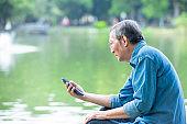 elder man use smart phone