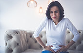 Menstrual pain. Sad woman is sitting on a couch and holding her lower stomach with both hands, while suffering from menstrual cramps.
