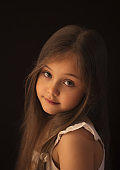 portrait of a little beautiful girl with long hair against a dark background