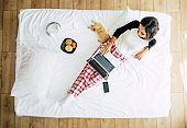 Full-length top view photo of a young brunette woman in casual clothes while she works with a laptop in bed. Happy girl studying with a dog at home