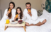 Happy young beautiful family in bathrobes are taking morning breakfast in a luxury hotel room. Service in the room. Vacation and trip