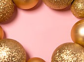 Pink Christmas background with golden balls. New Year and Christmas 2021. Place for text.