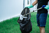Man hand use garbage collector equipment keeping plastic waste into black bag at park.