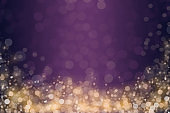 Abstract shiny golden bokeh glitter and sprinkles on purple gradient background