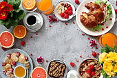 Breakfast food table. Festive brunch set, meal variety with pancakes, juice, fresh berries, granola and fresh fruits.