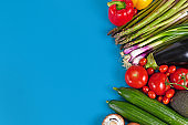 Healthy vegetables background with tomatoes, bell pepper, spring onions, eggplant, asparagus, cucumber and avocado on blue blank copy space